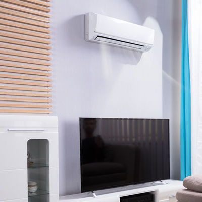 AC on wall above a tv