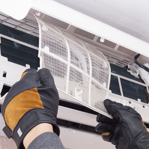 specialist cleans and repairs the wall air conditioner
