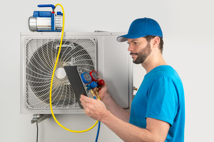 Technican evacuates the system with vacuum pump and manifold gauges