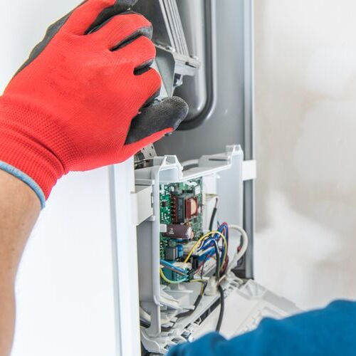 Technician Servicing Residential Heating Equipment.